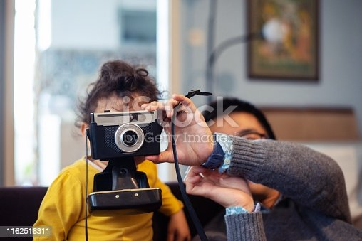 A little girl playing with a film camera at home.