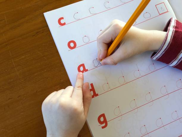 Child learning to write Child practicing writing letters of the alphabet illiteracy stock pictures, royalty-free photos & images