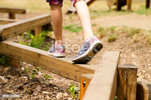 Child leg play balance on wooden beam in park.