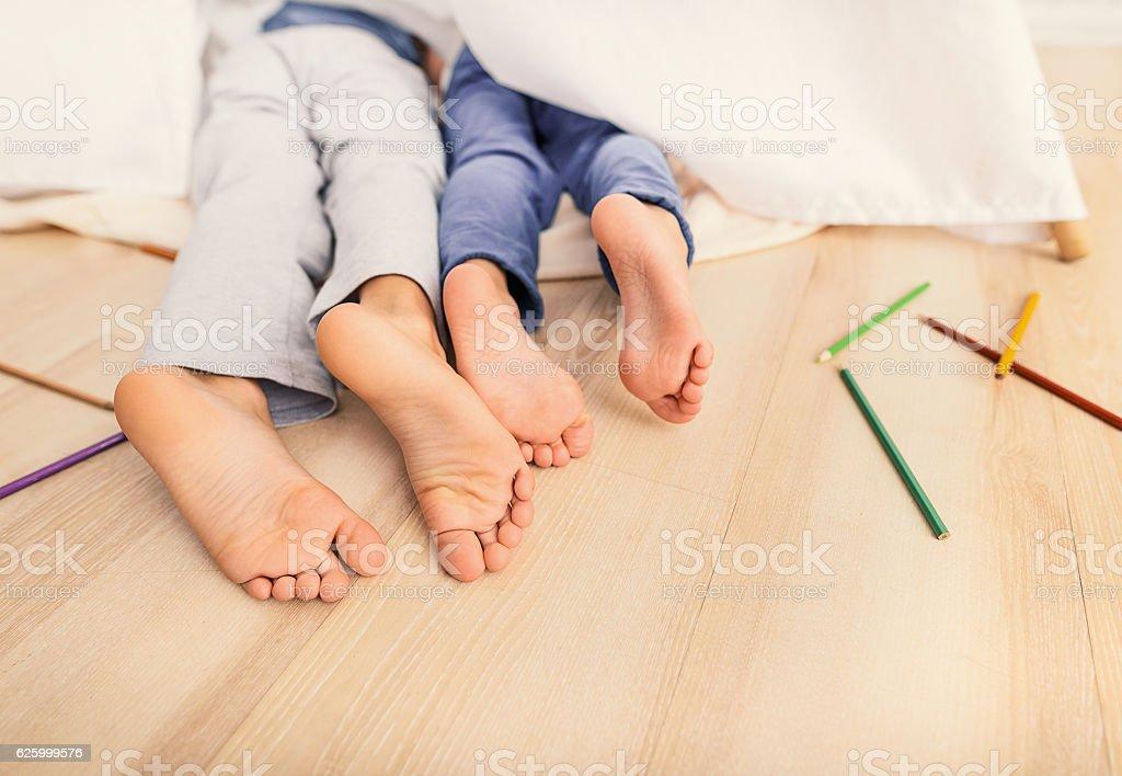 Child legs under white blanket stock photo