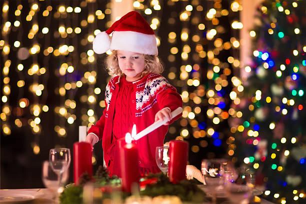 kind beleuchtung ein candle at christmas dinner - kinderzimmer tischleuchten stock-fotos und bilder