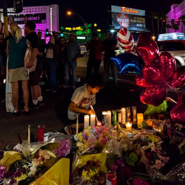 Enfant s'allume bougies lors d'une veillée de memorial des victimes sur le Las Vegas Boulevard en face de l'emplacement de la Route 91 Festival - Photo