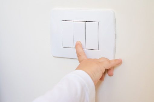 Child Little Boy Turning On The White Lightswitch With His