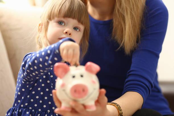 çocuk paraları servet koyarak küçük kız kol - bearn stok fotoğraflar ve resimler