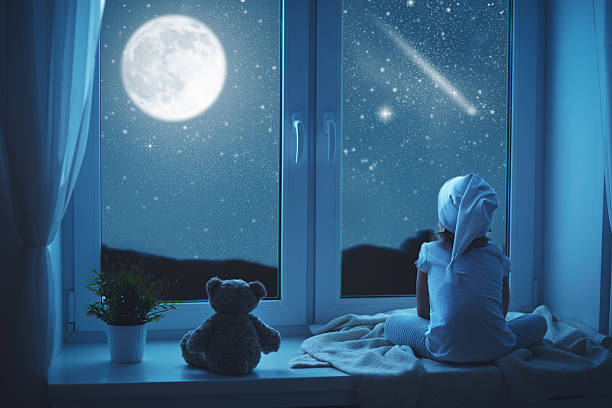 child little girl at window dreaming and admiring starry sky stock photo