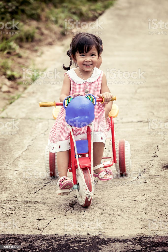 ad3898dec97 Child little girl having fun to ride tricycle with sister - Stock image .