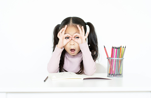 1019302738 istock photo Child little girl is through her fingers in ok gesture and keeps mouth opened on the white room while drawing. 1128962560