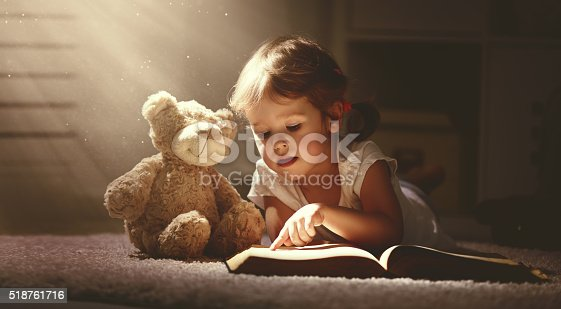 istock child little girl reading a magic book in dark home 518761716