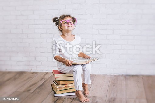 istock Child little girl sitting on a stack of books with glasses 907929330