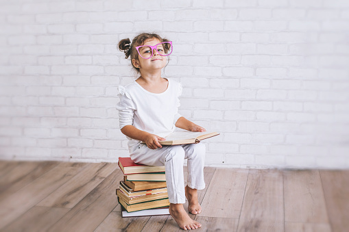 Child little girl sitting on a stack of books with glasses