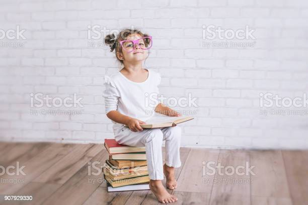 Child little girl sitting on a stack of books with glasses picture id907929330?b=1&k=6&m=907929330&s=612x612&h=psl3bsxq2pbzi1rkud 36ufen1kh6ya3oxlzoce8nq8=