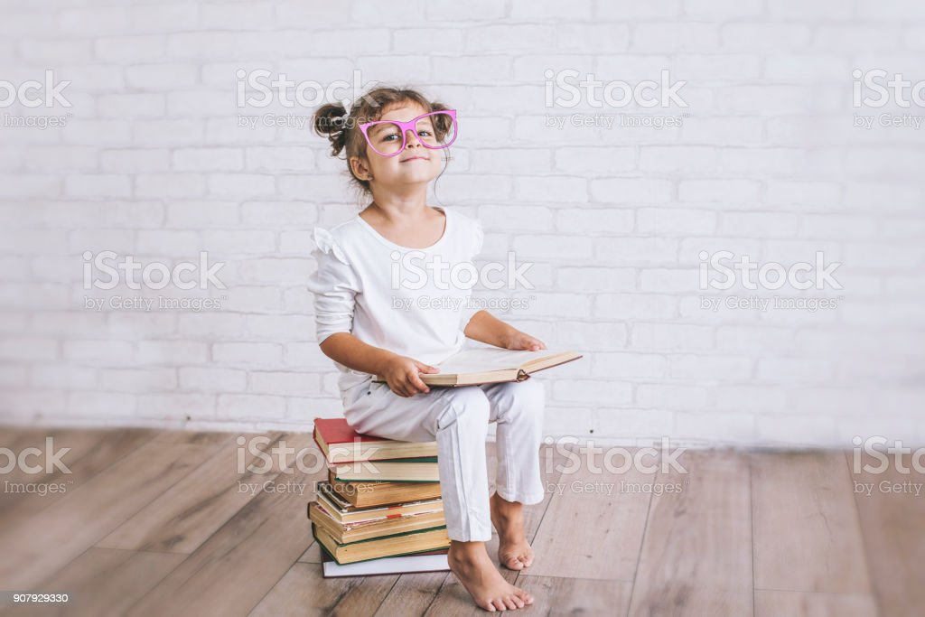 Child little girl sitting on a stack of books with glasses stock photo