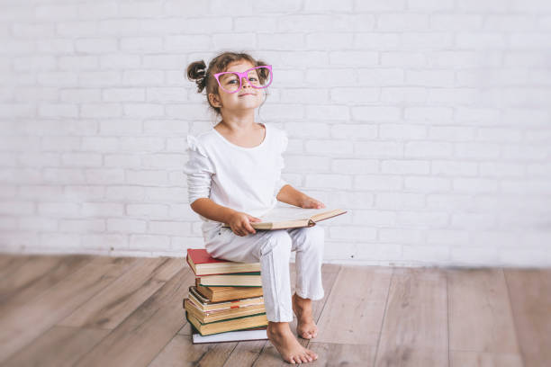 child little girl sitting on a stack of books with glasses - genius stock photos and pictures