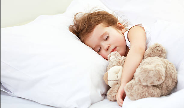 child little girl sleeps in the bed with teddy bear stock photo