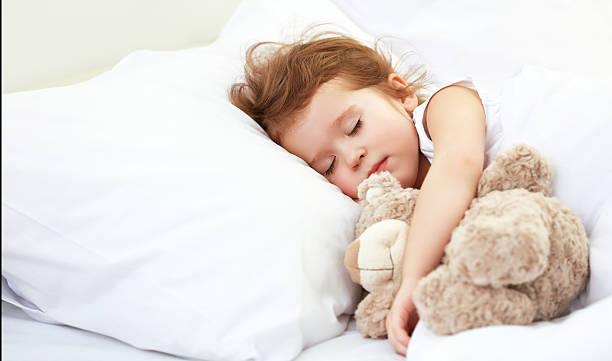 Criança garotinha dormir na cama com urso de pelúcia - foto de acervo