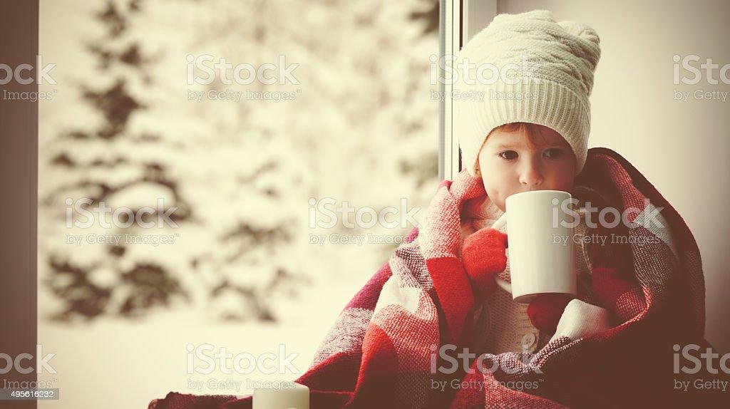 Enfants petite fille avec une tasse de thé chaud à la fenêtre - Photo