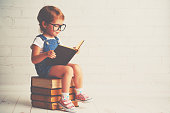 child little girl with glasses reading a books