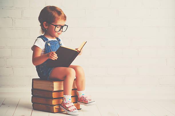 Child little girl with glasses reading a books picture id506584266?b=1&k=6&m=506584266&s=612x612&w=0&h=r3ys2osivetbf4mzkux 6eaywory8nr1qfrx3lc5kk8=