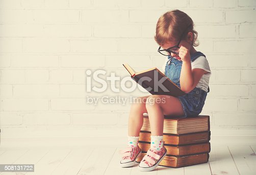 istock child little girl with glasses reading a books 508131722