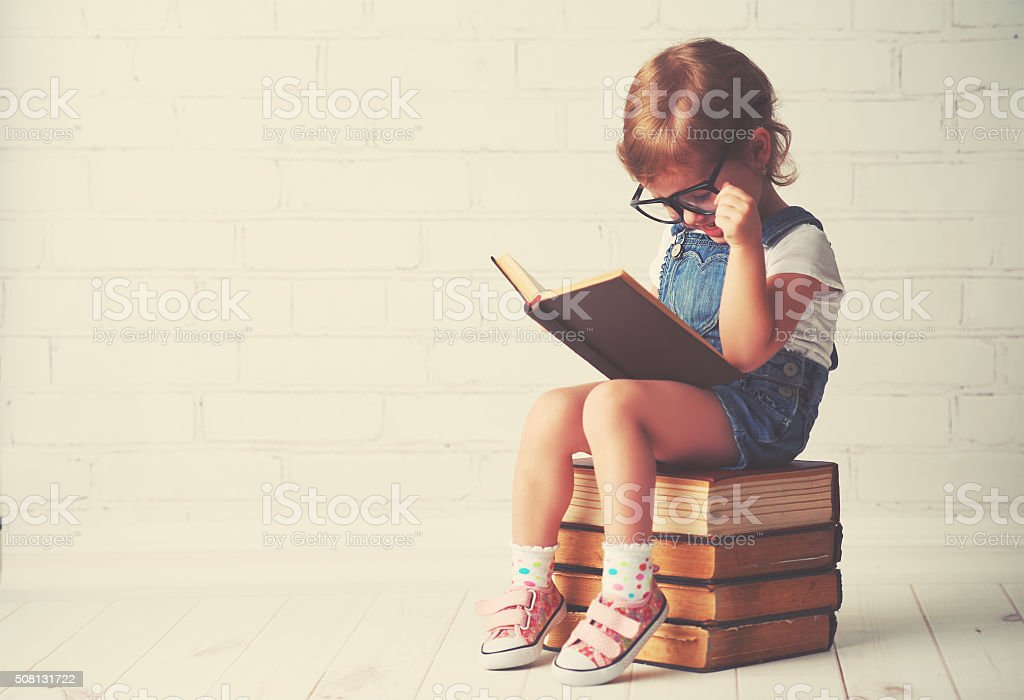 child little girl with glasses reading a books​​​ foto
