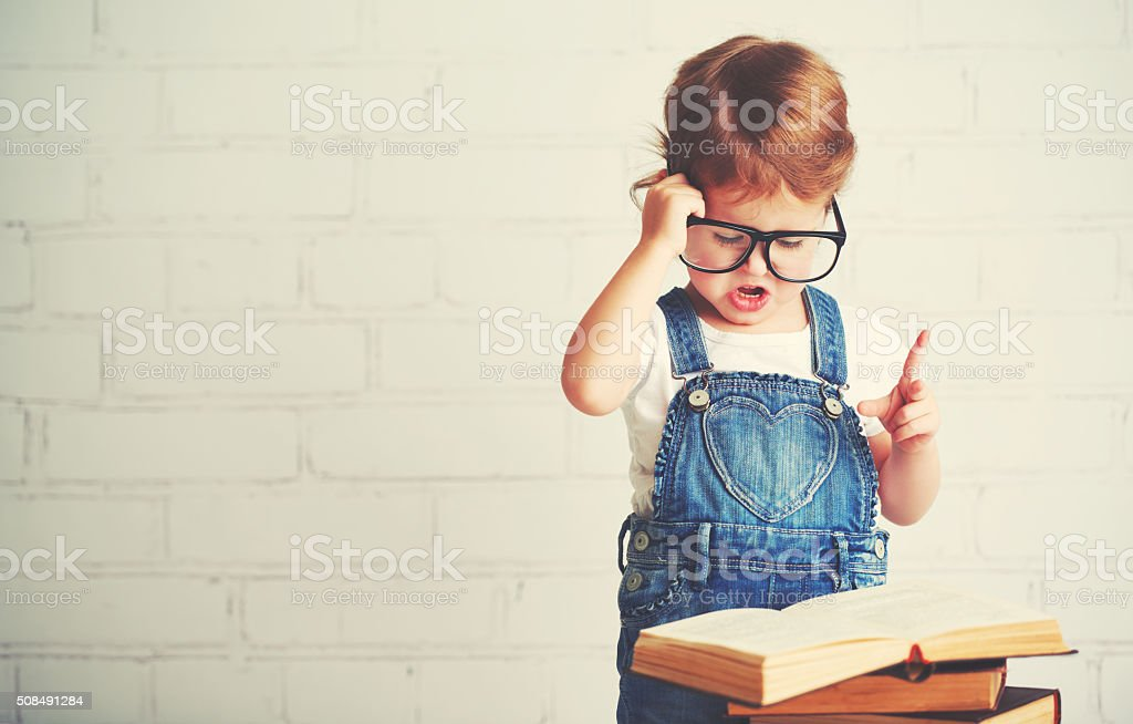 child little girl with glasses reading a books stock photo