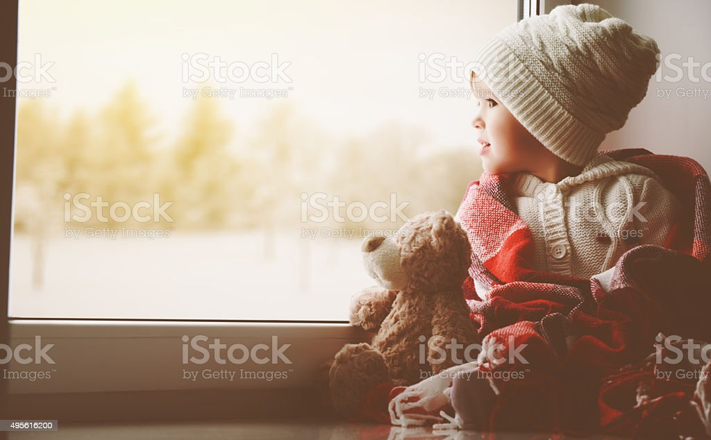 child little girl with  teddy bear at window stock photo