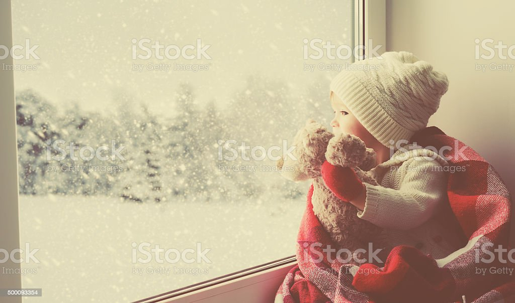 child little girl with  teddy bear at window winter child little girl sitting by the window with a teddy bear and looking at the winter forest Baby - Human Age Stock Photo