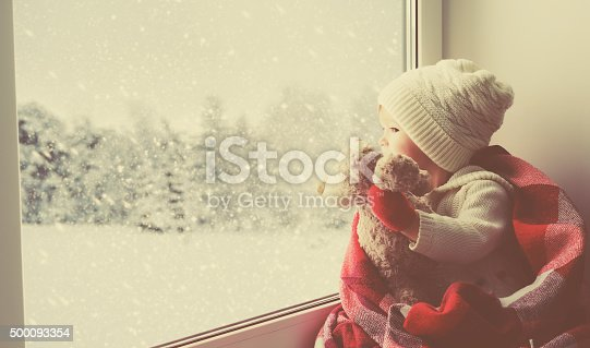 istock child little girl with  teddy bear at window winter 500093354