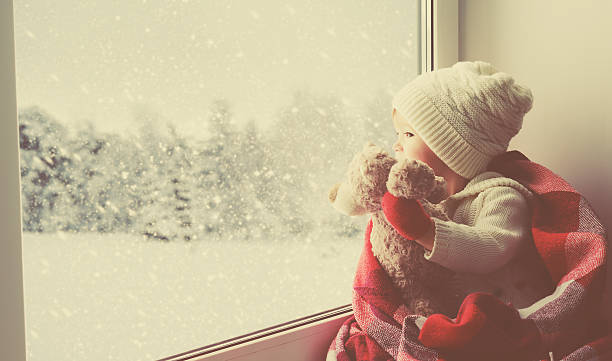 child little girl with  teddy bear at window winter stock photo