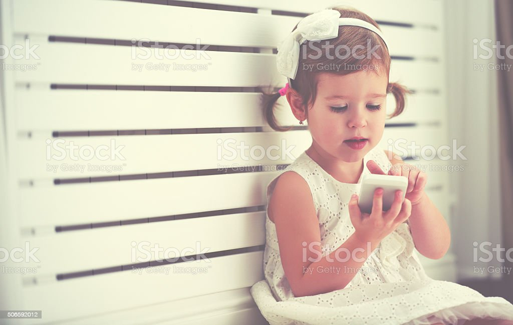child little girl with  telephone smartphone child little girl with a telephone smartphone Baby - Human Age Stock Photo