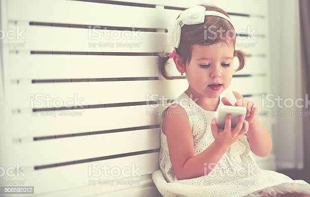 Child Little Girl With Telephone Smartphone Stock Photo - Download Image Now