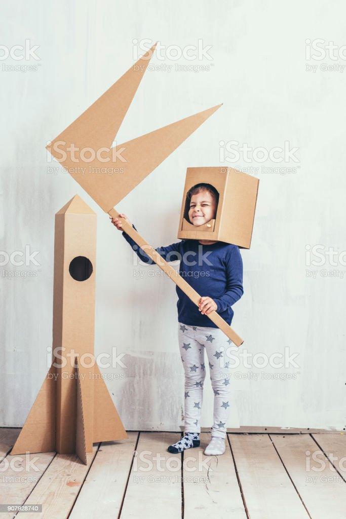Niños niñas jugando astronauta con un cohete de cartón y un casco de cartón - foto de stock