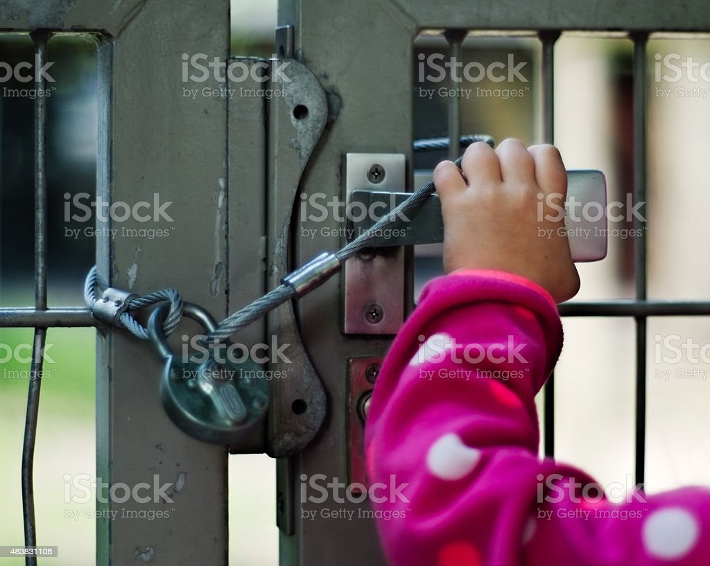Child locked up behind a fence stock photo