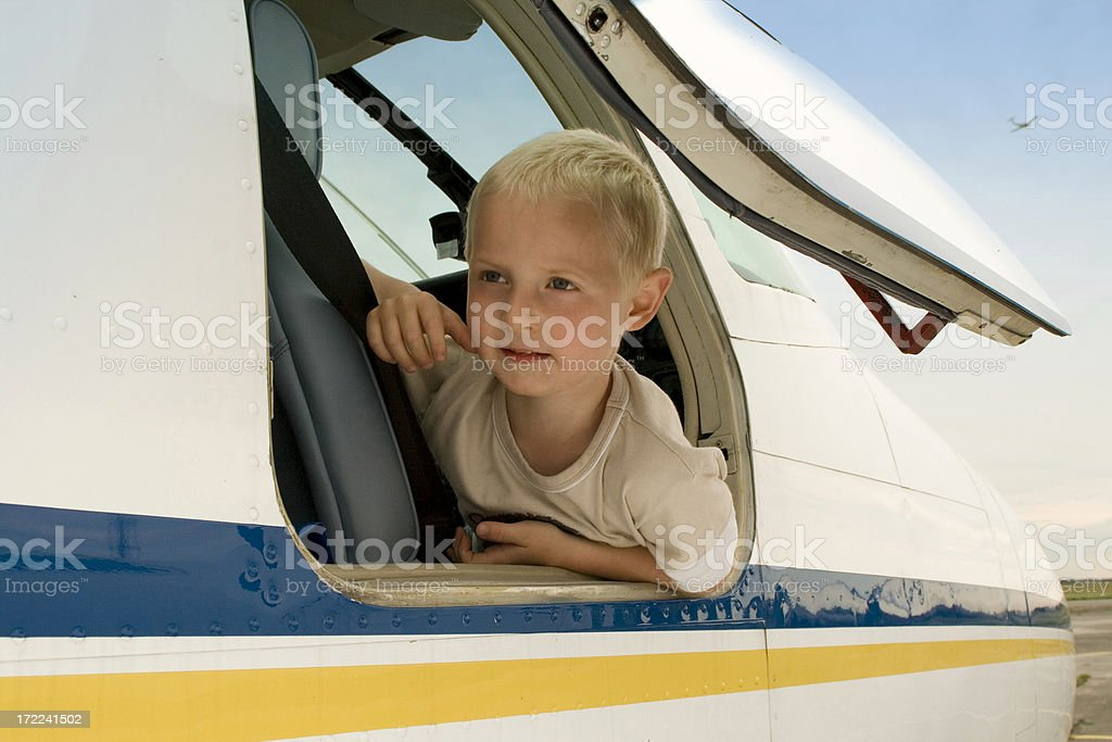 Child looking out from a plane door royalty-free stock photo