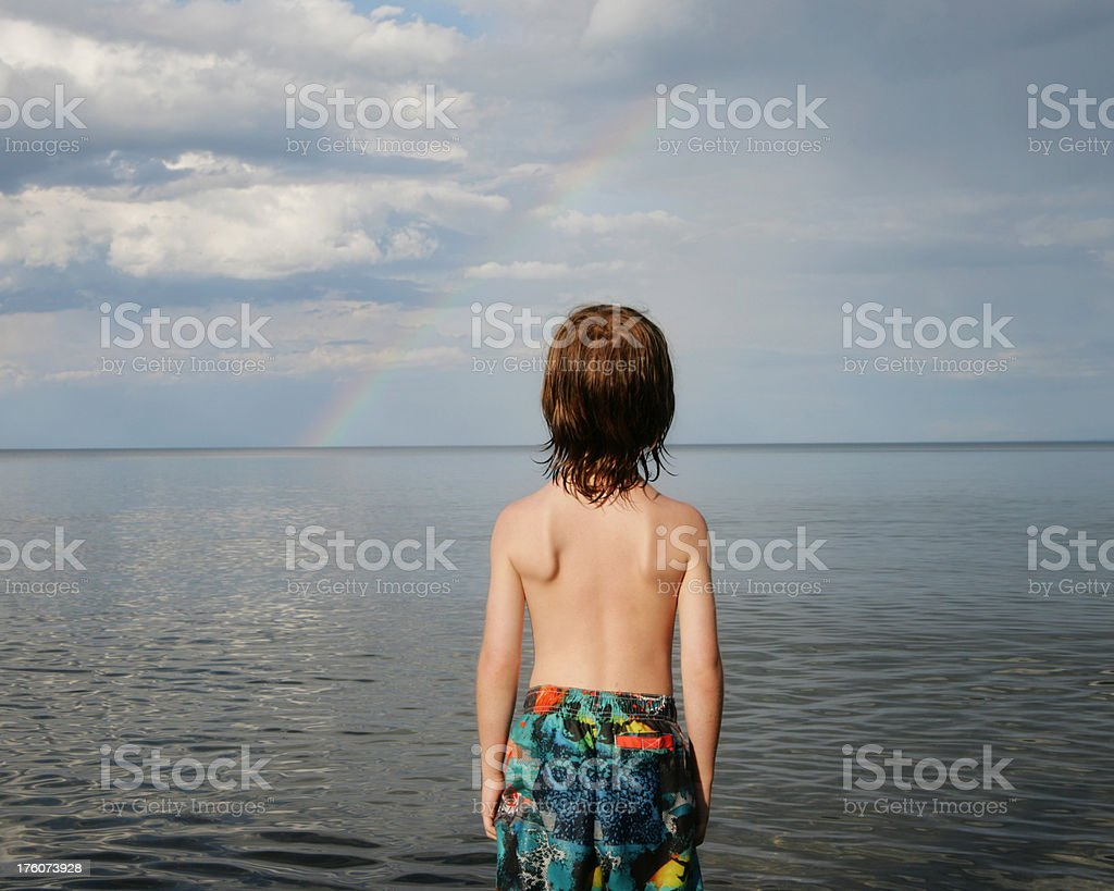 Child Looking Over Lake Superior Towards Rainbow stock photo