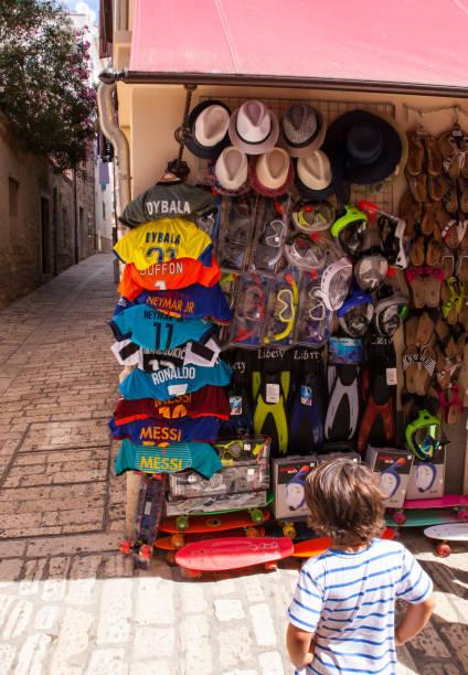 child looking soccer shirts hang outside a shop - ronaldo imagens e fotografias de stock