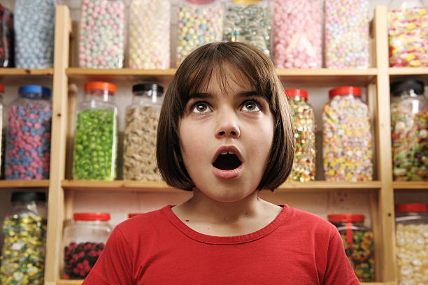 A child looking surprised in a sweet shop stock photo