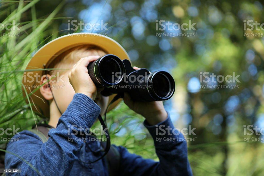 Child Looking Through Big Binoculars Outdoors stock photo