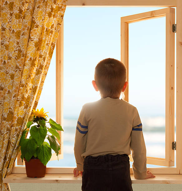 child looking through open window wooden - boy looking out window stock pictures, royalty-free photos & images