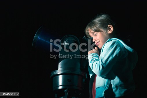 istock Child looking through telescope in the night 494583112