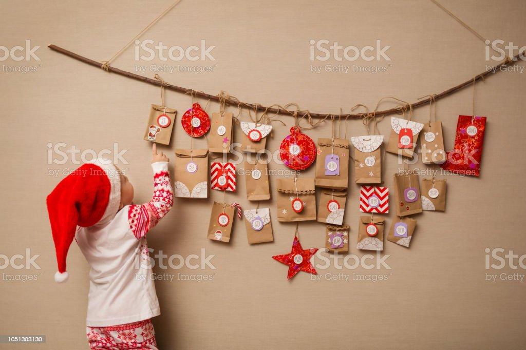 niño mira el calendario de Adviento. Niña en un sombrero de la Navidad y  pijamas be7b20054fc