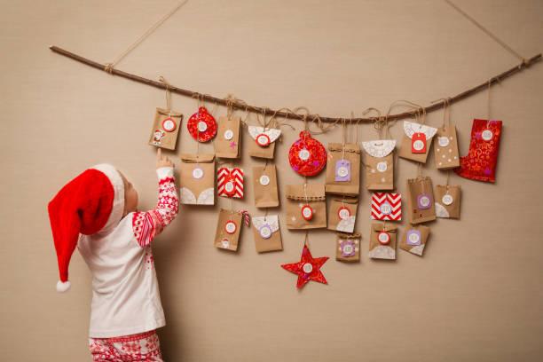 barn ser på julkalendern. baby flicka i en jul hatt och pyjamas visar på första gåva - advent bildbanksfoton och bilder