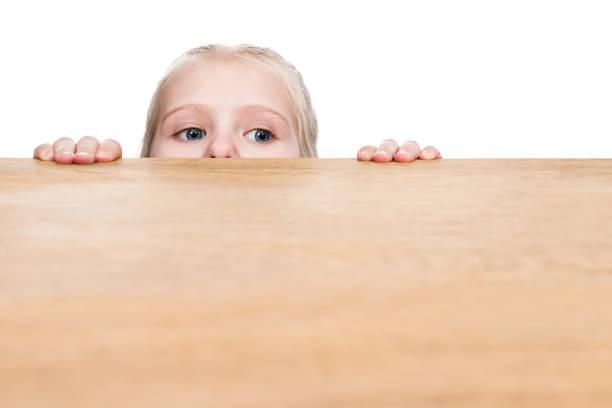kind schaut unter dem tisch - peeping tom stock-fotos und bilder