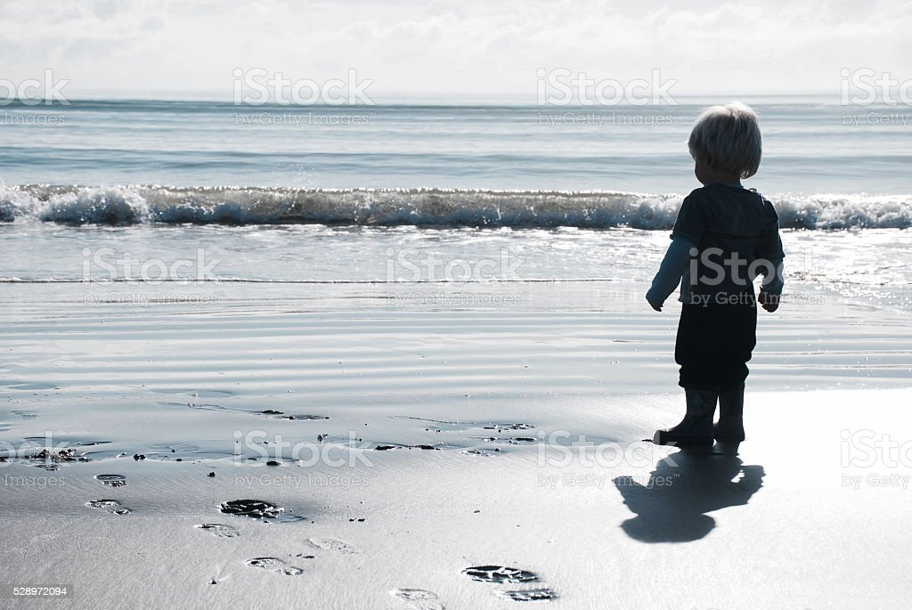 Child looks out to the Sea in Winter Sun stock photo