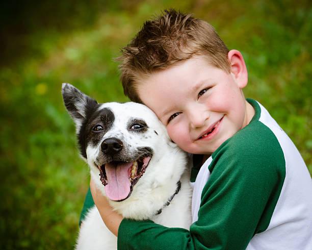 Child lovingly embraces his pet dog stock photo