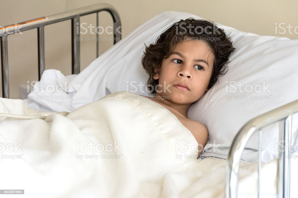 Child lying in hospital bed stock photo