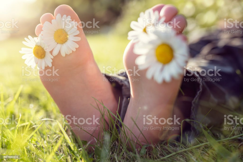 Child lying in meadow relaxing in summer sunshine stock photo