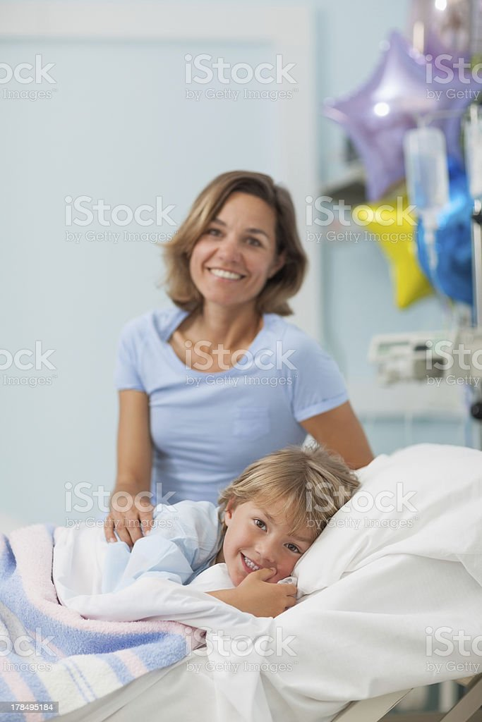 Child lying on a bed next to his mother royalty-free stock photo