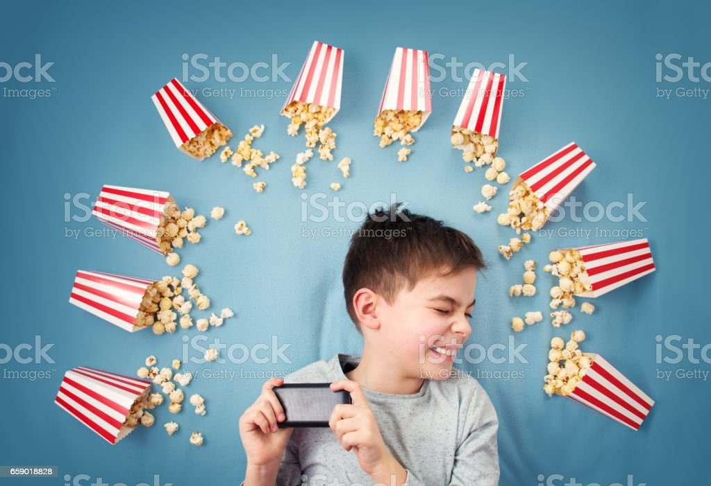 Child lying on blue background with smartphone and watching movie royalty-free stock photo