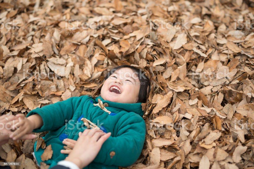 紅葉のヒープ上に横たわる子 ストックフォト